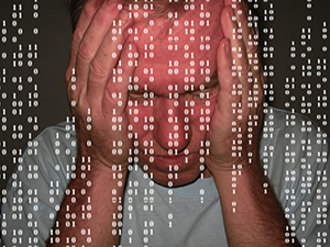 Man with head in hands, behind foreground of ones and zeros like matrix