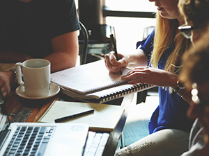 Woman at coffee shop taking notes in meeting
